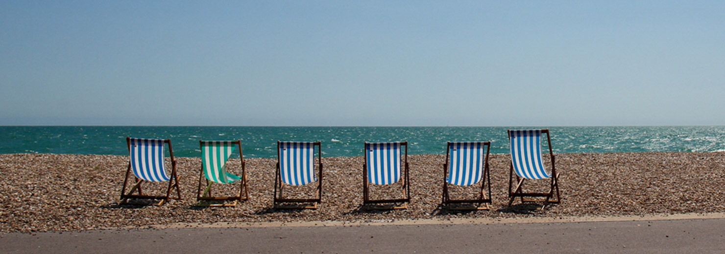 A row of 6 empty deckchairs on the promenade facing the sea